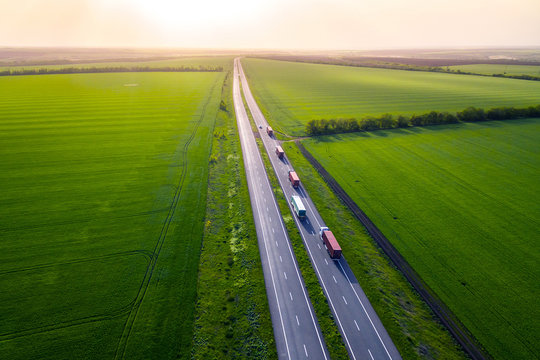 trucks on the higthway sunset. cargo delivery driving on asphalt road along the green fields. seen from the air. Aerial view landscape. drone photography.