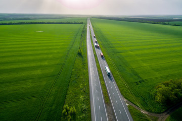 convoys with cargo. trucks on the higthway sunset. cargo delivery driving on asphalt road along the green fields. seen from the air. Aerial view landscape. drone photography. Wall mural