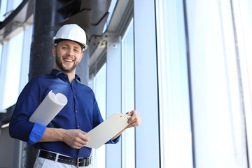 Shot of smiling male architect wearing hardhat and inspecting new building.