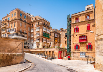 Fotomurales - Historic city centre of Valletta, Malta. Beautiful architecture with traditional balconies and red old telephone box along the street.