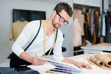 Young male designer of fashion looking at textile samples in catalogue