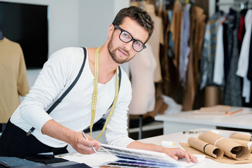 Young professional fashion designer with measuring tape looking at you