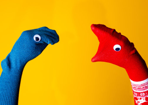 Red and blue sock puppets argue on the colorful yellow background
