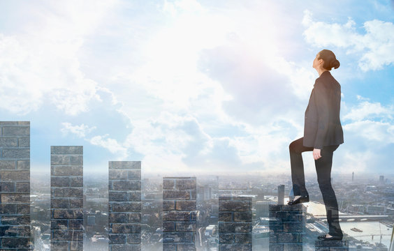 Young woman climbing up on the growth bars and looking positive to the future. Blue sky and sunshine. Business, success and strategy concept
