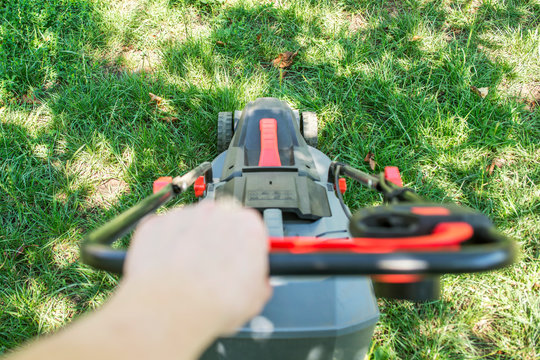 Lawn mowing and gardening. The interesting point of view from a man pushing a lawn mower