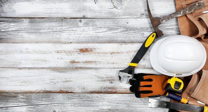 Labor Day concept with industrial worker tools over distressed white wooden background