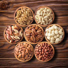 various nuts in wooden bowls, top view. food background: pecan, hazelnut, walnuts, almonds,...