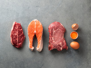 Carnivore or keto diet concept. Raw ingredients for zero carb or low carb diet - rib eye, salmon steak, pork, egg on gray stone background. Top view or flat lay. - fototapety na wymiar