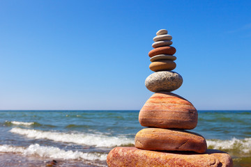 Zen pyramid of balanced stones on a background of the summer sea and blue sky