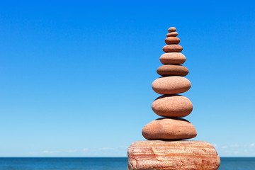 High Rock zen pyramid of pink stones on a background of blue sky and sea.