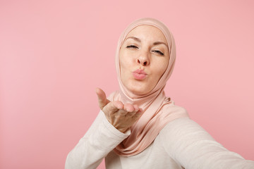 Close up arabian muslim woman in hijab light clothes posing isolated on pink background. People religious lifestyle concept. Mock up copy space. Doing selfie shot on mobile phone, sending air kiss.