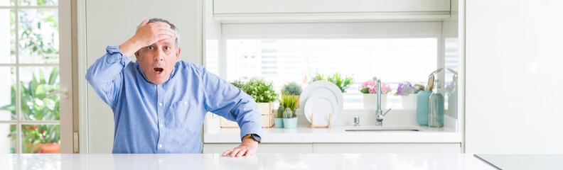 Wide angle perspective of handsome senior man at home surprised with hand on head for mistake, remember error. Forgot, bad memory concept. Wall mural