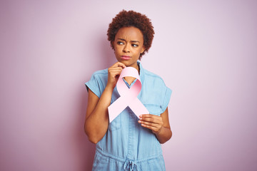 Young african american woman holding brest cancer ribbon over isolated pink background serious face thinking about question, very confused idea