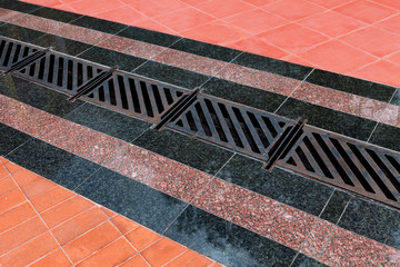 Pedestrian covering, lined with granite tiles with metal drainage grate.