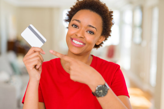 Young african american woman holding credit card very happy pointing with hand and finger