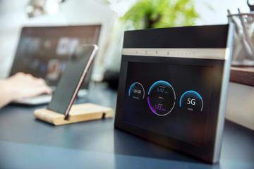 Modern 5G wi-fi router with display on the desk and devices on the background. Interface on the screen was created in graphic program.