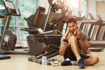 Full length portrait of handsome man sitting on floor in gym and using smartphone, copy space