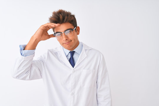 Young handsome sciencist man wearing glasses and coat over isolated white background worried and stressed about a problem with hand on forehead, nervous and anxious for crisis