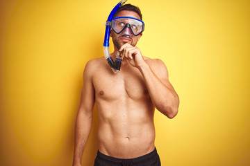 Young handsome shirtless man wearing diving goggles over isolated yellow background serious face thinking about question, very confused idea Wall mural