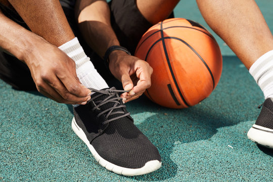 Closeup of African-American man tying sports shoes in basketball court outdoors, copy space background