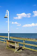 A lamppost next to a bench on the Ocean View fishing pier in Norfolk, Virginia.