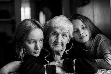 An elderly woman is photographed with two granddaughters. Black and white photo.
