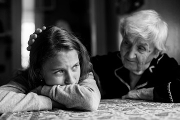 A little girl cries, her grandmother pats her hand on the head. Black and white photo.