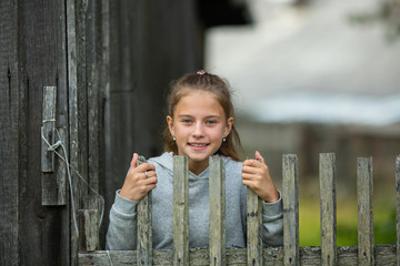Portrait of Little cute girl near a wooden fence in the countryside.