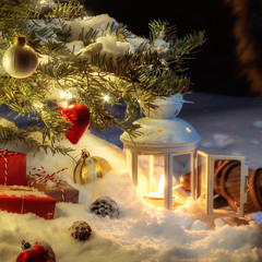 Christmas composition - a tree in the snow, gifts, decoration and a hand lighting a lantern with a match