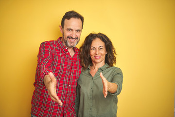 Beautiful middle age couple over isolated yellow background smiling friendly offering handshake as...