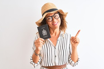 Senior tourist woman holding Canadian Canada passport over isolated white background very happy...