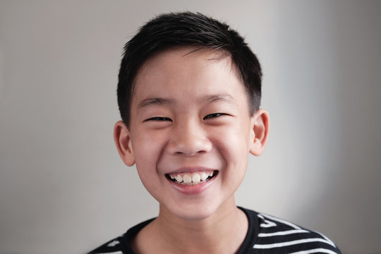 Head shot portrait of happy, confident and healthy mixed race multiethnic smiling Asian preteen teen boy face, youth day