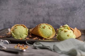 Balls of pistachio ice cream in waffle cones on a dark background.