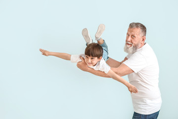Cute little boy playing with grandfather on light background
