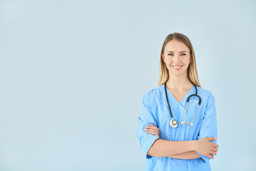 Female nurse with stethoscope on color background Fototapete