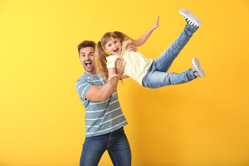 Happy father playing with daughter on color background