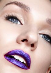 Closeup macro shot of human woman face makeup and bright violet lips