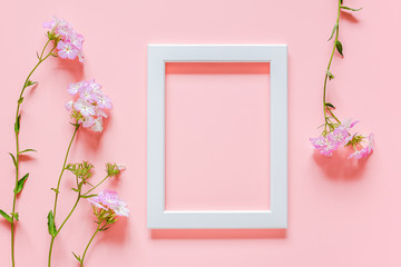 White wooden picture frame and flowers on pink background with copy space. Creative Top view Flat lay Mock up Template for invitstion, greeting card