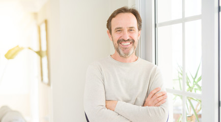 Handsome middle age man smiling looking at the camera at home