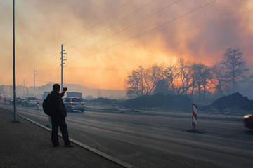 KRAKOW, POLAND - MARCH 28, 2012: The man is taking a picture with a smartphone during a big fire