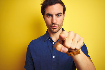 Young handsome man with tattoo wearing casual shirt standing over isolated yellow background pointing with finger to the camera and to you, hand sign, positive and confident gesture from the front