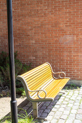 A sidewalk bench in the city offers an inviting spot to rest in the sun