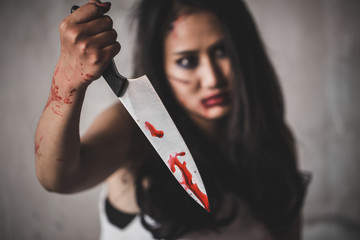Horror Picture of a female killer at bloody knife honding hand with scary face, Depression and fear.