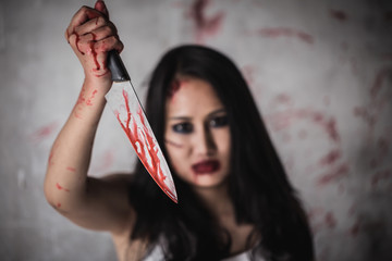 Horror Picture of a female killer at bloody knife honding hand with scary face.