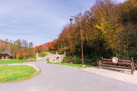 beautiful park in the mountains. wonderful sunny autumn weather. trees in fall foliage. lanterns and benches along the walking path, blue sky with clouds
