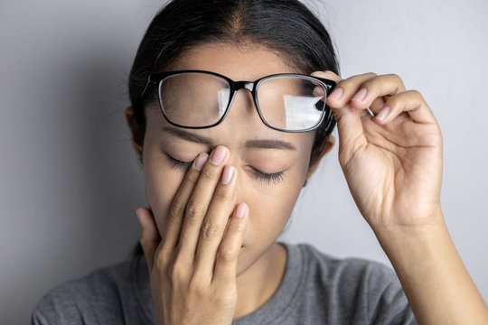 Women hold glasses and suffer from eye pain.