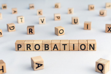 probation - word from wooden blocks with letters, time criminal is allowed to stay out of prison or period a new employee is suitable for work concept, random letters around, white  background
