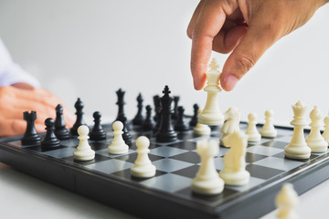 hand of businessman moving chess in competition, shows leadership, followers and business success strategies