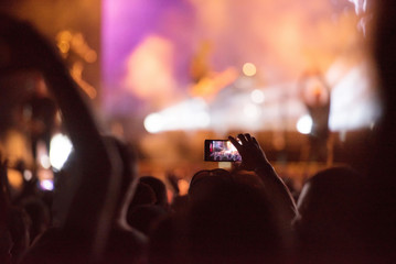 People taking photos with smart phones during a mconcert
