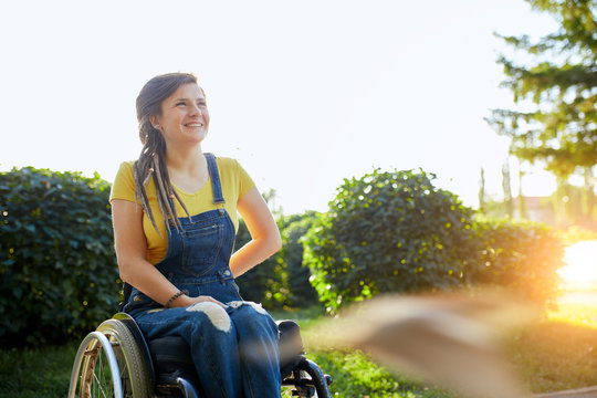 beautiful disabled girl looking up, looking at the bright side of life, woman gets pleasure from the beauty of nature, landscape. copy space